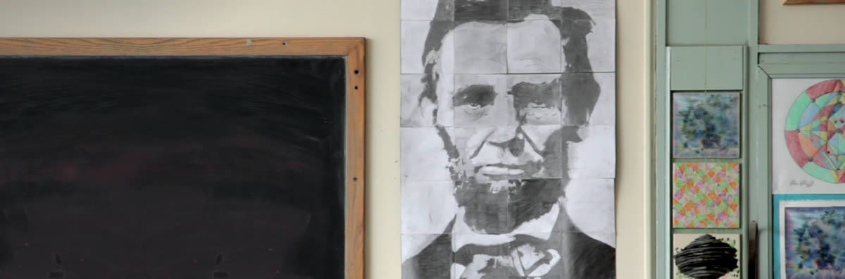 Classroom chalkboard with drawing of Abraham Lincoln taped to the wall next to it