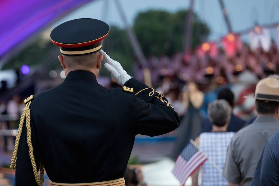 A service member salutes the flag as Sofia Carson sings the National Anthem at <em>A Capitol Fourth</em> at U.S. Capitol, West Lawn on July 4, 2017 in Washington, DC.