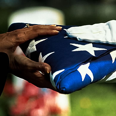 hands passing a folded flag