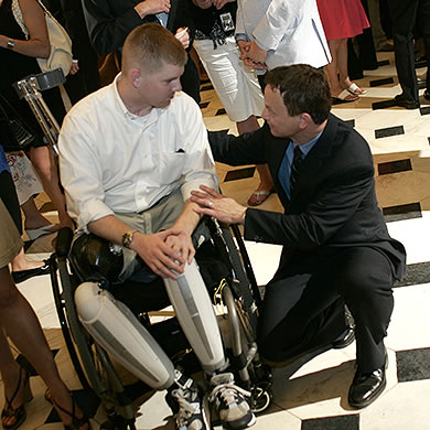Gary Sinise with a soldier in a wheel chair with artificial legs