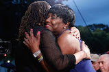 Actress S. Epatha Merkerson (L) gives a hug to Gold Star mother Paula Davis after paying tribute to her son, Army Private First Class Justin R. Davis, who was killed in Afghanistan, at the 27th <em>National Memorial Day Concert</em>.