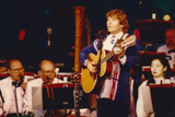 John Denver performs with the National Symphony Orchestra, led by Maestro Erich Kunzel, on the 1995 <i>National Memorial Day Concert</i>.