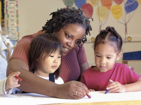 A childcare provider sitting at a table with two young children and they are coloring