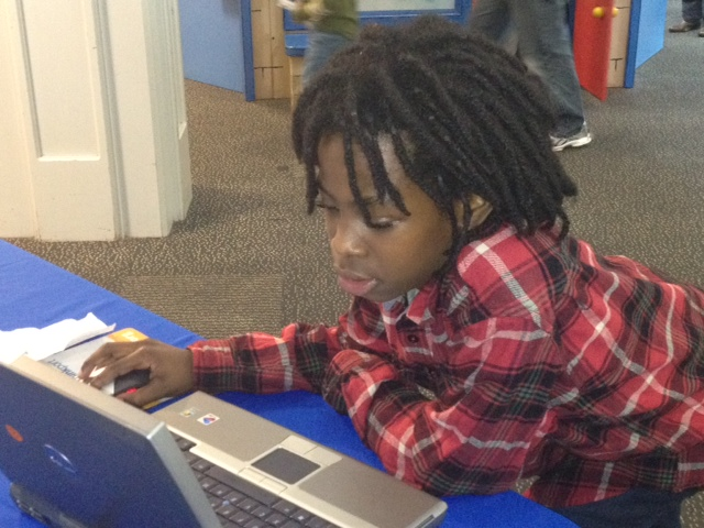A young boy leaning over a table and playing with a laptop computer at a community event in Baltimore.