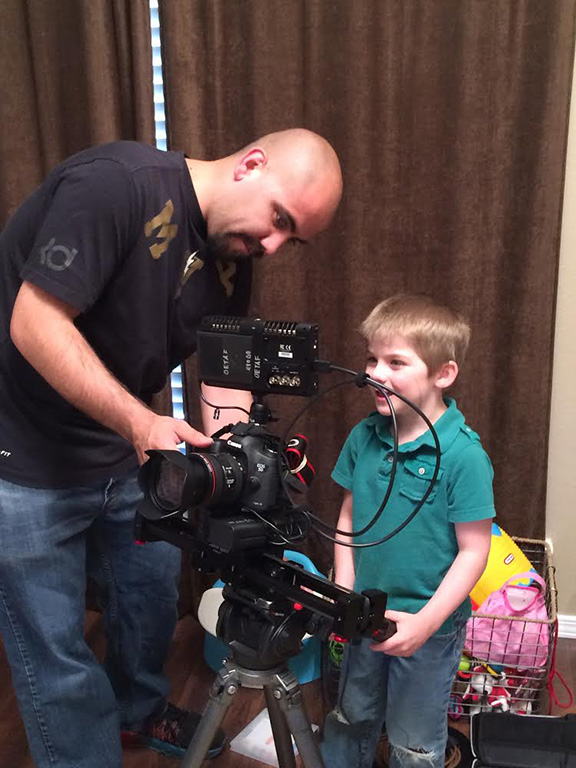 OETA Production Assistant Carlos Manzano shows Gavin Cox, 5, how to set up a camera shot.