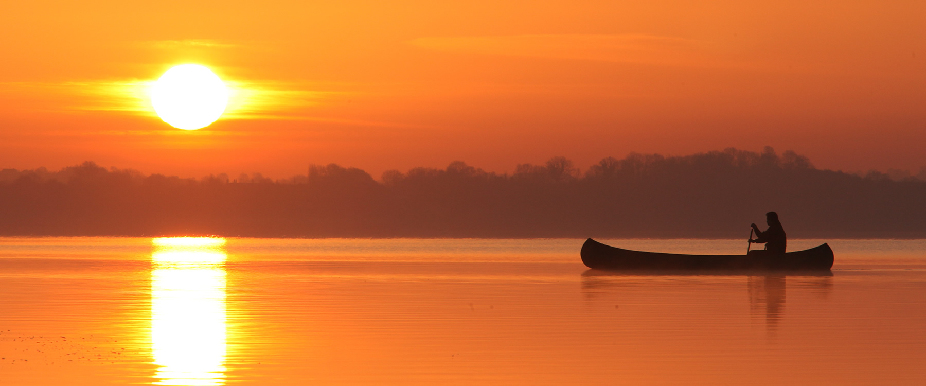 Person paddling in a canoe on a river at sunrise