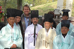 Michael Wood standing with men dressed in ceremonial clothing