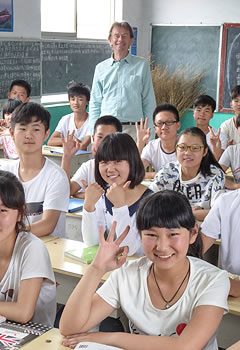 students seated at desks with Michael Wood standing behind them