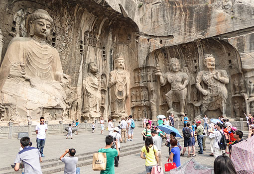tourists in front of large Buddhist sculptures carved into a cliff