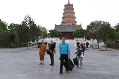 Michael Wood walking with film crew and monk in front of golden pagoda