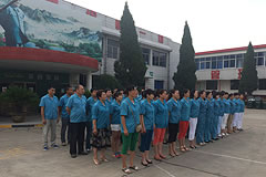 people wearing blue shirts standing lined up in rows outside a factory building