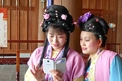 2 women in traditional costume looking at a smart phone